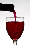 Red wine pouring down from a wine bottle Stock Photos