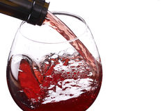 Red wine pouring down from a wine bottle. Isolated in white Royalty Free Stock Image