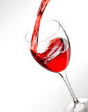 Red wine pouring into glass. On gray background stock image