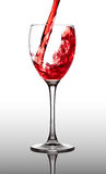 Red wine pouring into glass Stock Image
