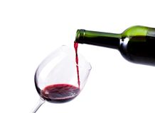 Red wine pouring in the glass. Isolated over white background Royalty Free Stock Image