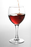 Red wine pouring into glass. Red wine pouring into wine glass Royalty Free Stock Image