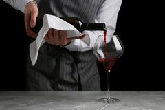 Red wine pouring in glass. bartender on waiter concept on black background royalty free stock image