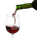 Red wine pouring in glass from a bottle  on white  Stock Photo