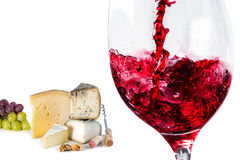 Red wine pouring in glass with cheese in background Royalty Free Stock Photos