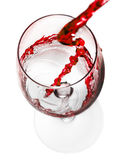 Red wine pouring in glass isolated on white background Royalty Free Stock Images