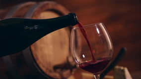 Red wine. Pouring red wine into glass in old cellar