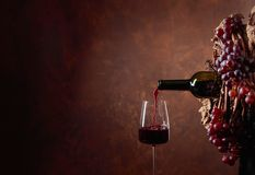 Red wine pouring into a glass. Conceptual image on the theme of winemaking. Copy space for your text royalty free stock photo