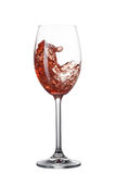 Red wine pouring into glass with splash isolated on white Royalty Free Stock Images
