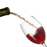 Red wine pouring into glass with splash isolated on white Royalty Free Stock Photo