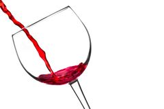 Red wine pouring into glass tilted with space for text Royalty Free Stock Image