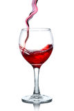 Red wine pouring in glass  on white Royalty Free Stock Images