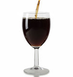 Red wine pouring into glass on white Royalty Free Stock Photography