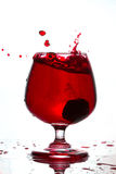 Red wine pouring into a glass on white background Royalty Free Stock Images