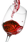 Red wine pouring in glass  on white background Royalty Free Stock Photo