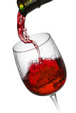 Red wine pouring in glass  on white background Royalty Free Stock Image