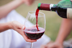 Red wine pouring into wine glass. Wedding royalty free stock photos