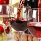 Red wine pouring into a wine glass. Fresh red wine pouring into a wine glass. Selective focus on the red wine Stock Photos