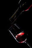 Red wine pouring into wine glass on black Royalty Free Stock Photos