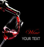 Red wine pouring into a wine glass. Red wine pouring into a glass from bottle. Isolated on black Stock Images