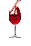 Red wine pouring into wine glass isolated Stock Image