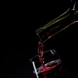 Red wine pouring into wine glass isolated on black Stock Photo