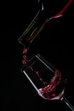 Red wine pouring into wine glass isolated on black Stock Photography