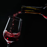 Red wine pouring into wine glass isolated on black Royalty Free Stock Photo
