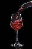 Red wine pouring into a wine glass Royalty Free Stock Photos