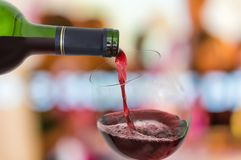 Red wine pouring into a wine glass Stock Images