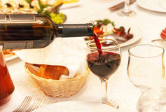 Red wine pouring into a wine glass, that standing on the table. Red wine is pouring from the bottle into a wine glass, that standing on the table in the royalty free stock photography