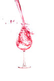 Red wine pouring  into wine glass on a white background Stock Photos