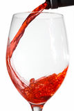 Red wine pouring into wine glass from a wine bottl Royalty Free Stock Image