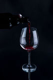 Red wine pouring into a wineglass. Isolated on black background. Stock Photos