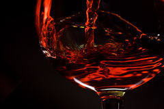 Red wine pours into a glass. Red wine pouring into a wineglass isolated on black background Stock Photo