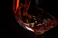 Red wine pours into a glass. Red wine pouring into a wineglass isolated on black background Royalty Free Stock Image