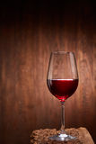 Red wine in the pure elegant wineglass standing on a wooden stand against wooden background. Stock Images