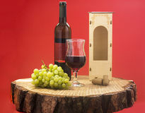 Red wine on a red background. Red wine and grapes on a red background stock photos