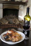 Red wine and roast piglet around the fireside Royalty Free Stock Photography