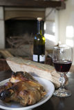 Red wine and roast piglet around the fireside Stock Photos