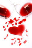 Red wine romance. Red wine spilled from glasses forming a heart shape Stock Image