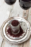 Red wine sea salt in a jar. With glasses of wine stock image