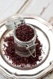 Red wine sea salt in a jar. On wooden background royalty free stock image