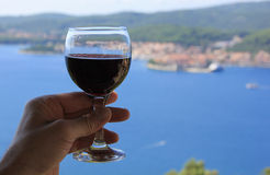 Red wine. Glass of red wine in hand. Croatian sea view, peninsula of Peljesac stock image