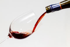 Red wine serve into the glass. The red wine serve into the transparency glass with white background Stock Photo
