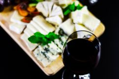 Red wine and set of different cheeses on a wooden board, delicio. Us snack, healthy and exclusive food Royalty Free Stock Photography