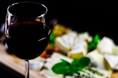 Red wine and set of different cheeses on a wooden board, delicio. Us snack, healthy and exclusive food Stock Photography