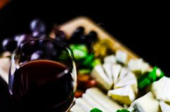 Red wine and set of different cheeses on a wooden board, delicio. Us snack, healthy and exclusive food Royalty Free Stock Images