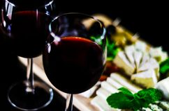 Red wine and set of different cheeses on a wooden board, delicio. Us snack, healthy and exclusive food Royalty Free Stock Image