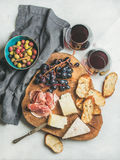 Red wine and snack set on board over grey background Royalty Free Stock Images